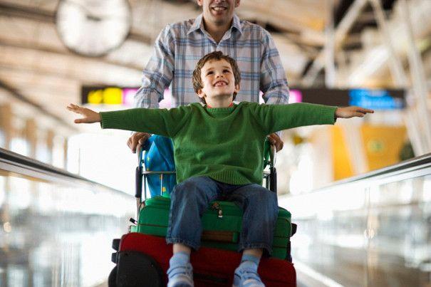 Мужчина везет мальчика на чемодане