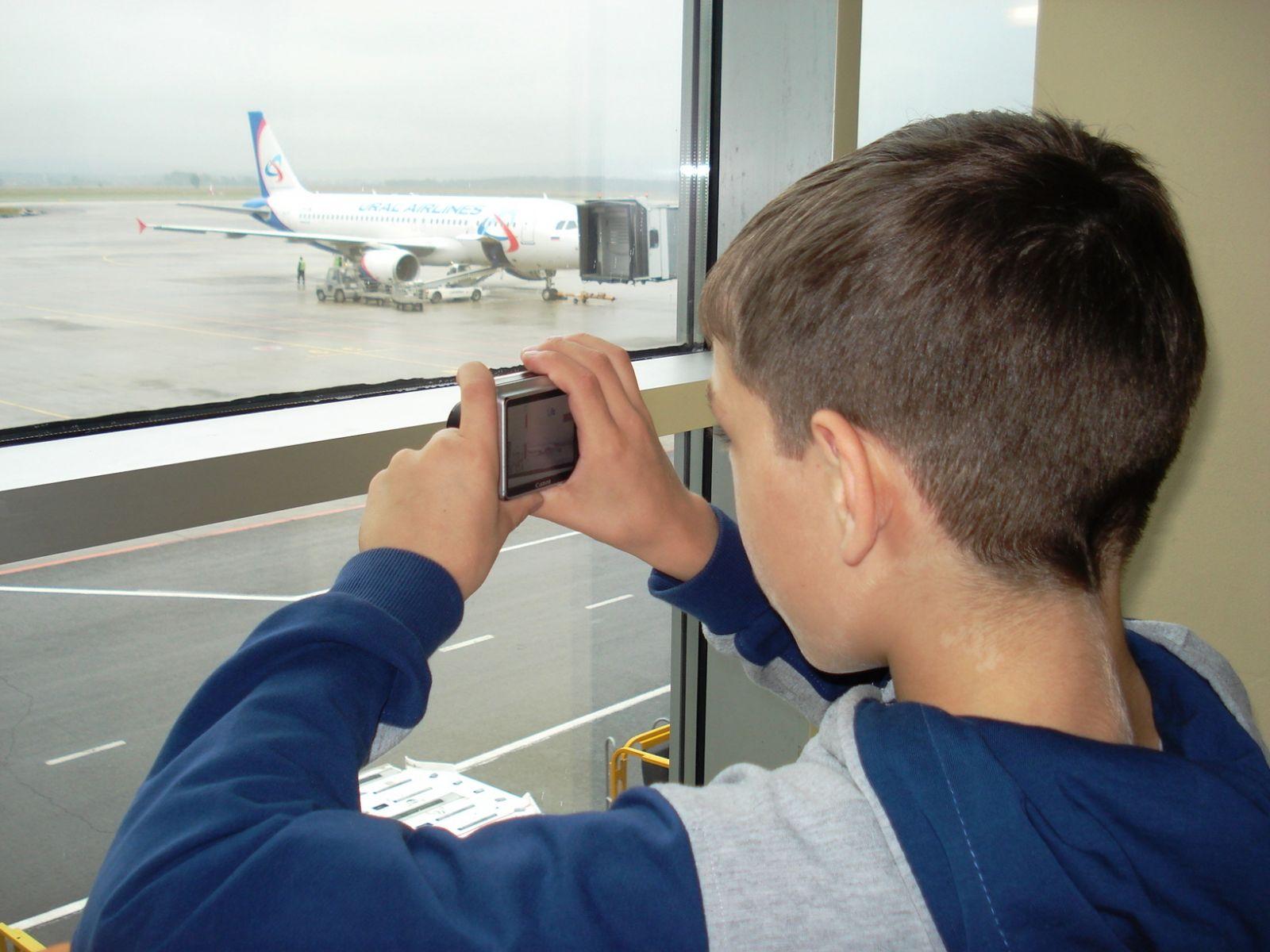 Мальчик фотографирует самолет