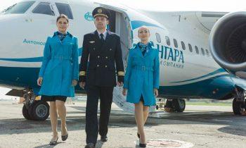 Пилот и стюардессы авиакомпании на фоне самолета