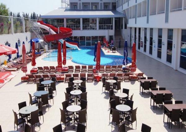 Территория отеля Dalaman Airport Lykia Resort Hotel со столами, стульями, водными горками, бассейном, зонтами и шезлонгами